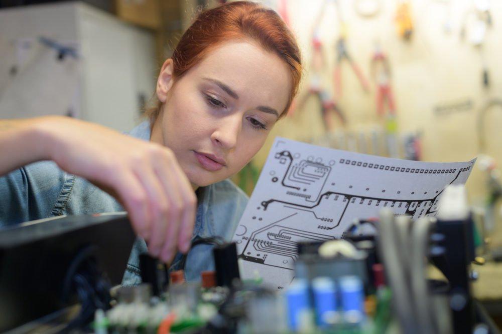 obrazek przedstawiający kobietę pracującą z rysunkiem okablowania nad instalacją